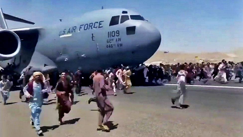Gente corre en la pista del aeropuerto de Kabul tratando de abordar un avión de la Fuerza Aérea de EE.UU.