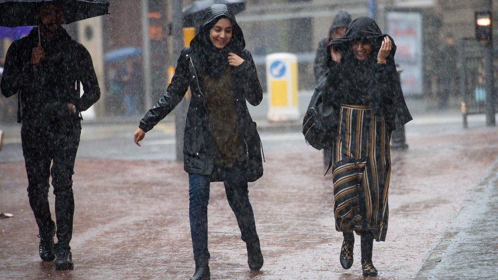 Two women and a man walk in the rain in Birmingham City
