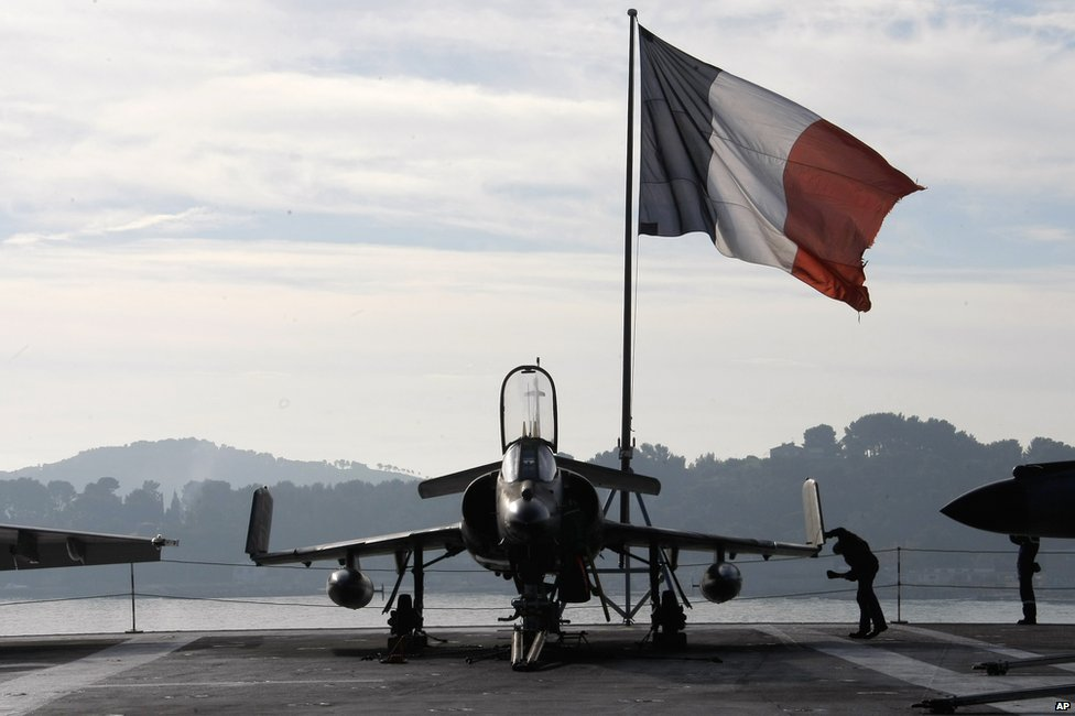 A French sailor checks a Super-Etendard jet on the deck of France's nuclear-powered aircraft carrier Charles de Gaulle in Toulon, 18 November