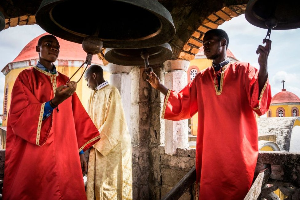 Men dressed in red clerical robes ring large church bells