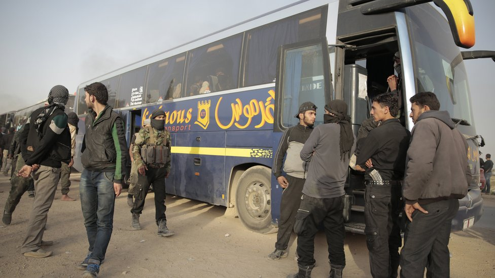 Rebel fighters stand near government-supplied buses in the countryside of Damascus, Syria, on 26 March 2018