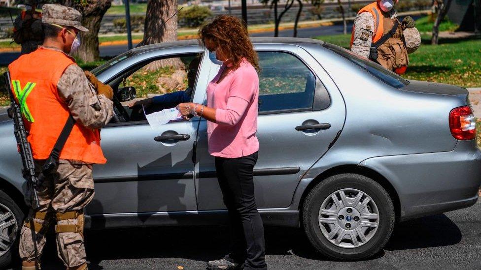 Mujer mostrando documentos a autoridades.