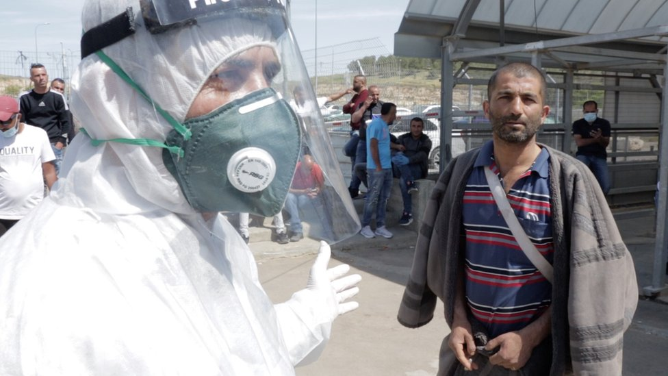 Zahid Soleiman is told by a medical worker to self-isolate at the Tarqumiya checkpoint, near the West Bank city of Hebron