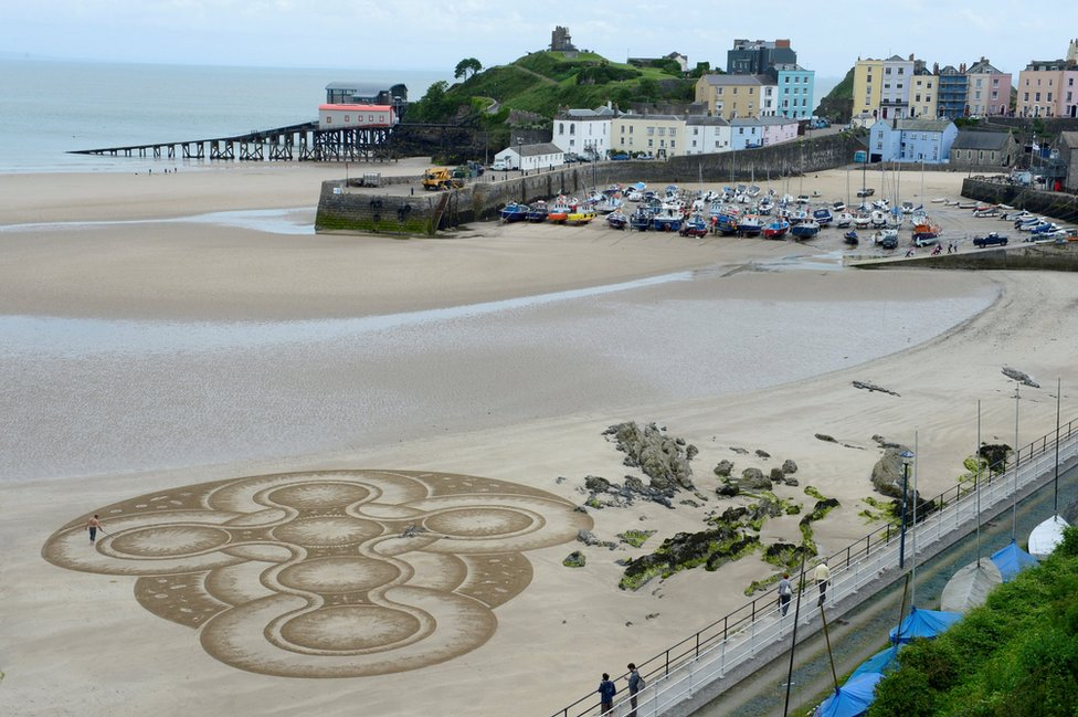 Sand artist Marc Treanor creates a work on the North Beach at Tenby Harbour, Pembrokeshire, Wales
