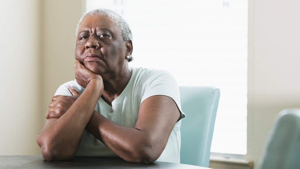 An ageing black woman looks seriously at the camera