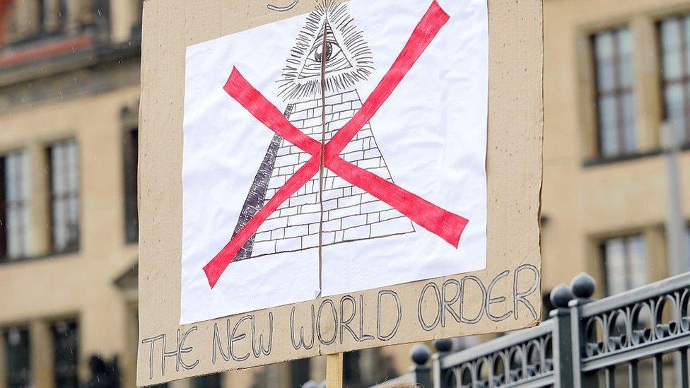"Demonstrant nosi parolu na kojoj piše ""Stop novom svetskom poretku"""