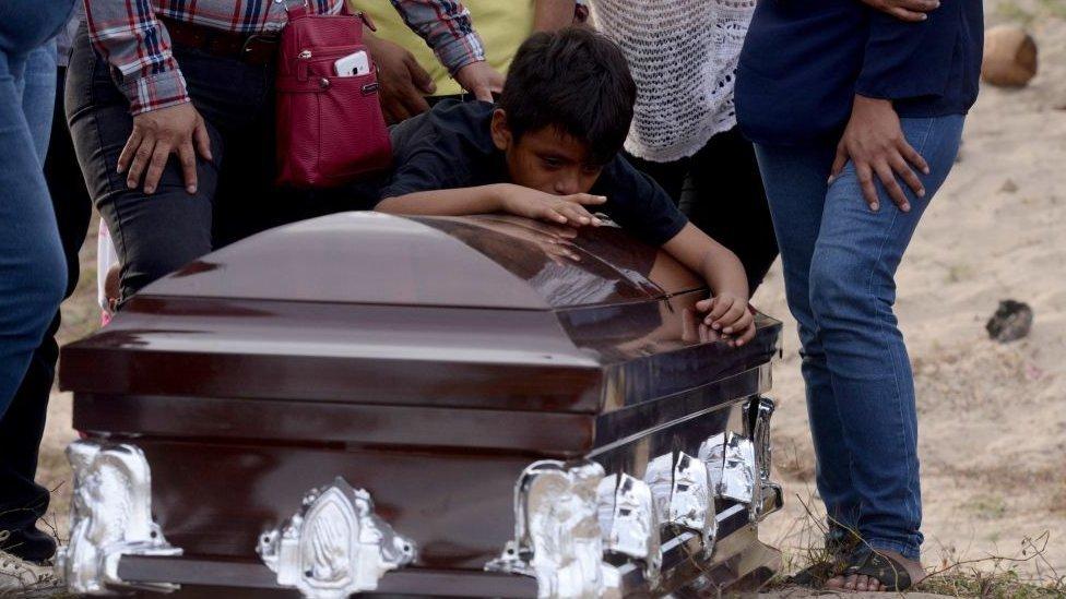 Familiares rodean el ataúd de una persona asesinada en México.