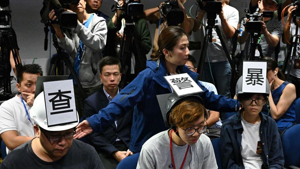 A police media relation officer (behind, C) stands behind six journalists (three not pictured), including Ronson Chan Ron-sing (L), a member of the executive committee of local media company Stand News, wearing protective press helmets with Chinese characters that collectively read Investigate Police Brutality Stop Police Lies in a press conference room at the police headquarters in Hong Kong on November 4, 2019,