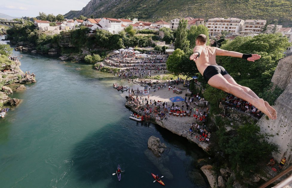 A man diving into water from a height into the Neretva river in Mostar