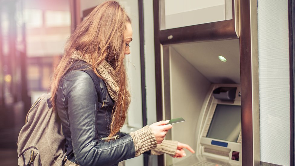 Young woman withdrawing cash from atm