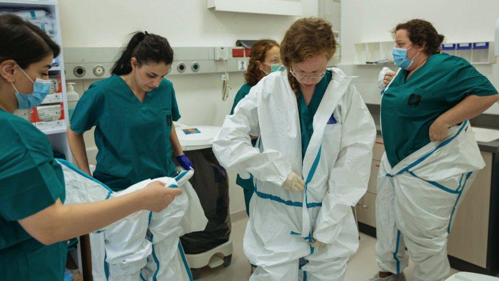 La dra. Limor Rubin (2a a la dcha) y enfermeras se ponen el equipo de protección mientras se preparan para ingresar a una sala aislada para tratar a pacientes con covid.