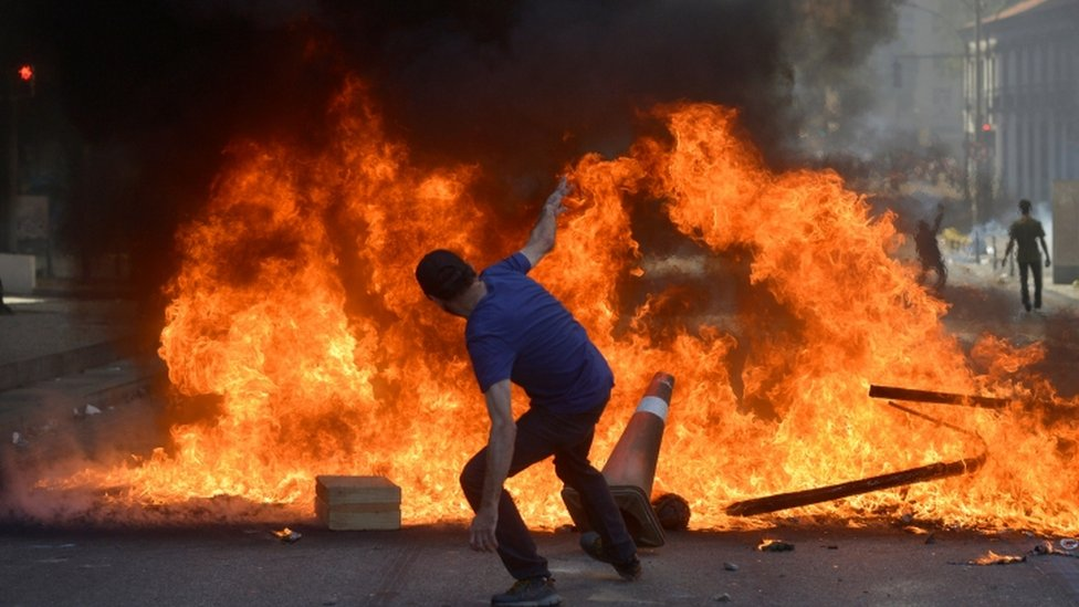 A protester throws a cone in a fire as he protests against spending cuts, 6 December