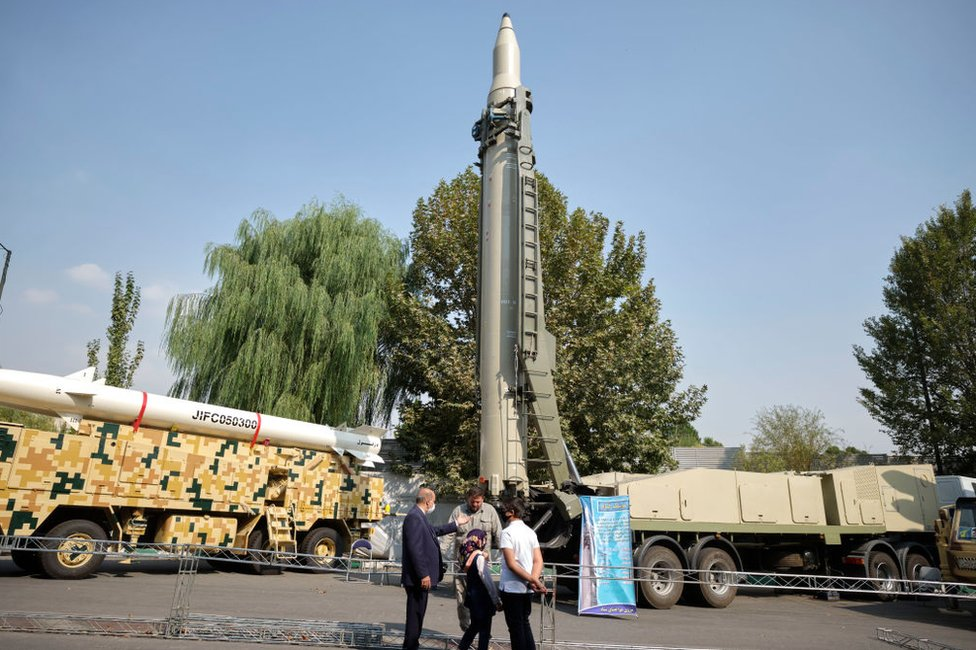 An Iranian family speaks with a member of the Islamic Revolution Guard Corps (IRGC) as they stand in front of a Qiam short-range ballistic missile, while visiting the Holy Defene Garden Museum in Tehran on 29 September 2020