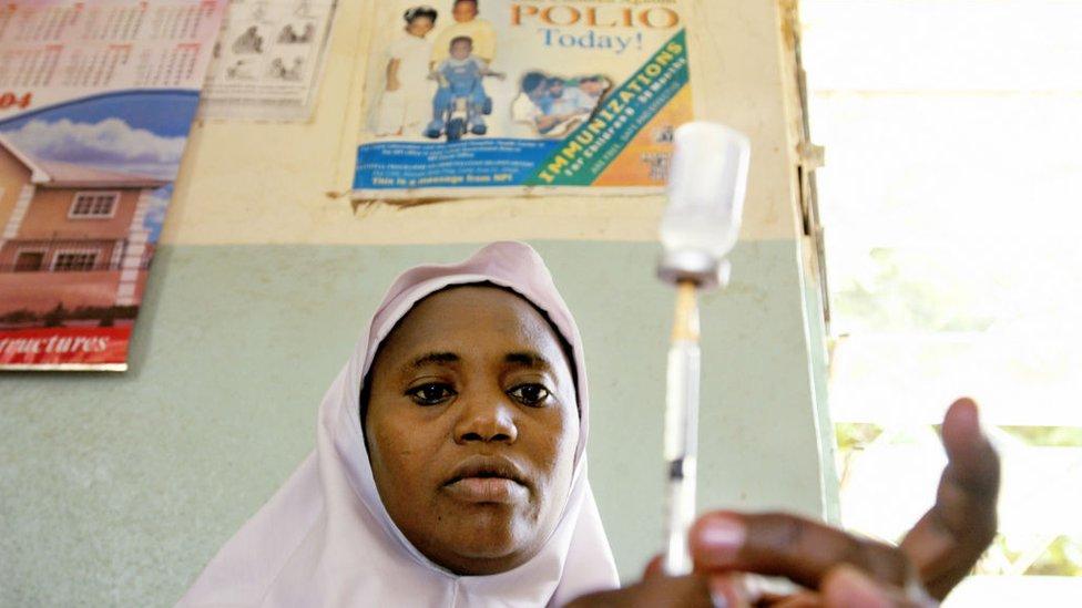 Una mujer prepara una vacuna contra la polio.