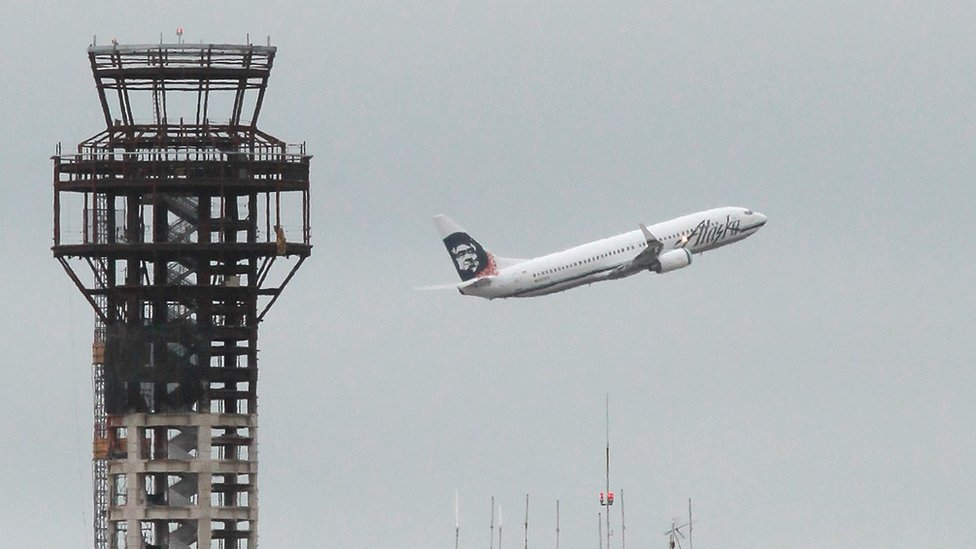 An Alaska Airlines plane takes off past a half-completed 236-foot FAA control tower (L) at Oakland International Airport on July 26, 2011 in Oakland, California.