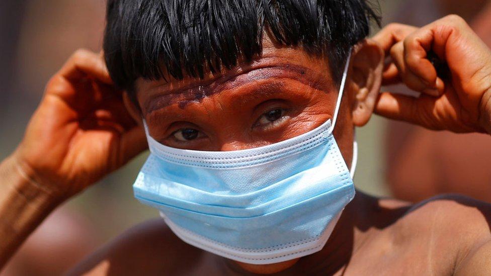 Homem do povo yanomami com pintura tradicional coloca máscara descartável