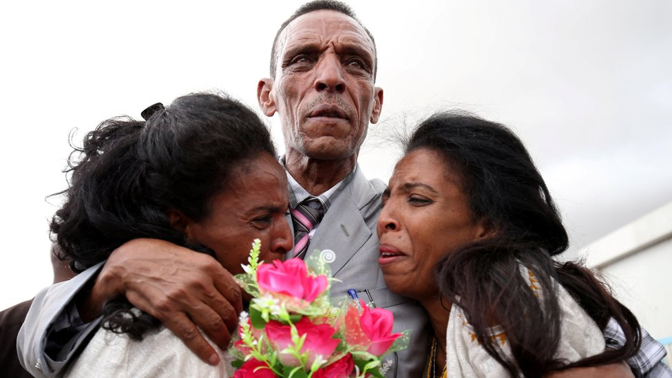 Adisalem Abu, reacts as he embraces his twin daughters, after meeting them for the first time in eighteen years, at Asmara International Airport after arriving aboard an Ethiopian Airlines flight in Asmara, Eritrea July 18, 2018.