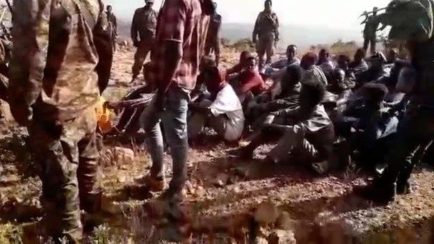 الفيديو يُظهر مجموعة من الرجال في زي مدني يجلسون على الأرض قبل المجزرة