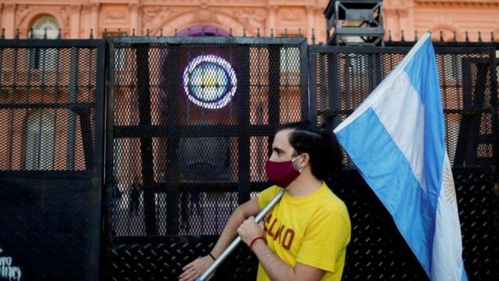 Homem segura a bandeira da Argentina durante protesto em frente à Casa Rosada, em Buenos Aires