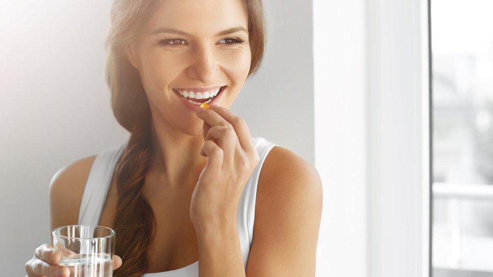 Woman taking omega-3 capsule