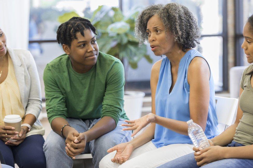 Jóvenes conversan con adultos.