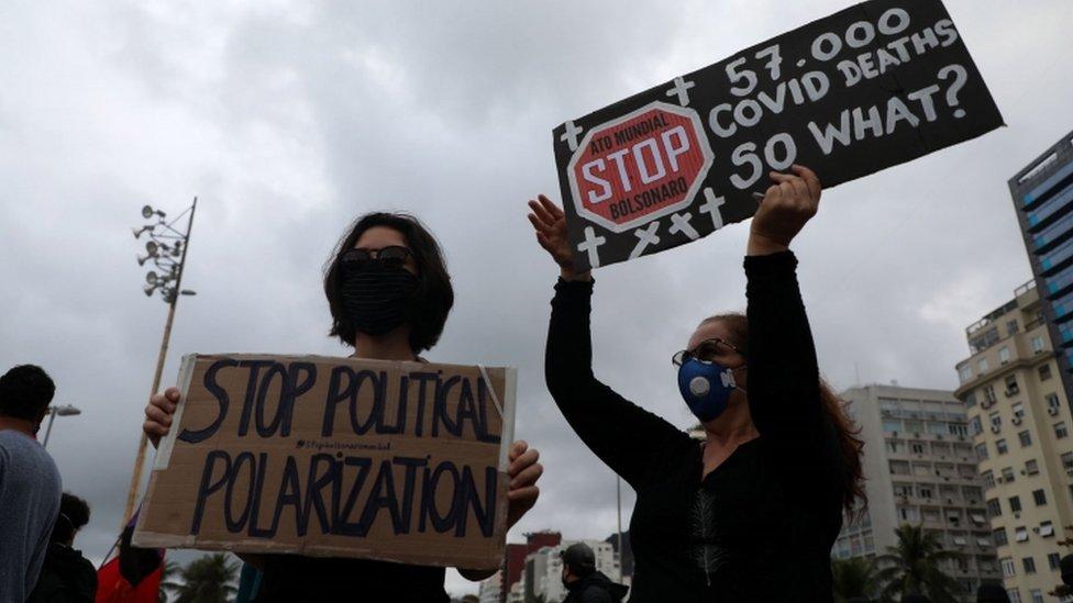 Duas mulheres, de máscara, seguram cartazes críticos a Bolsonaro em manifestação na rua