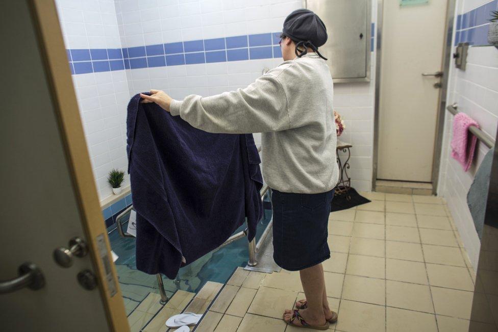 Una Balanit, o asistente de mikveh, sostiene una toalla para una mujer judía que entró a bañarse en Jerusalén, 17 de abril de 2019. (Foto: Heidi Levine para la BBC).