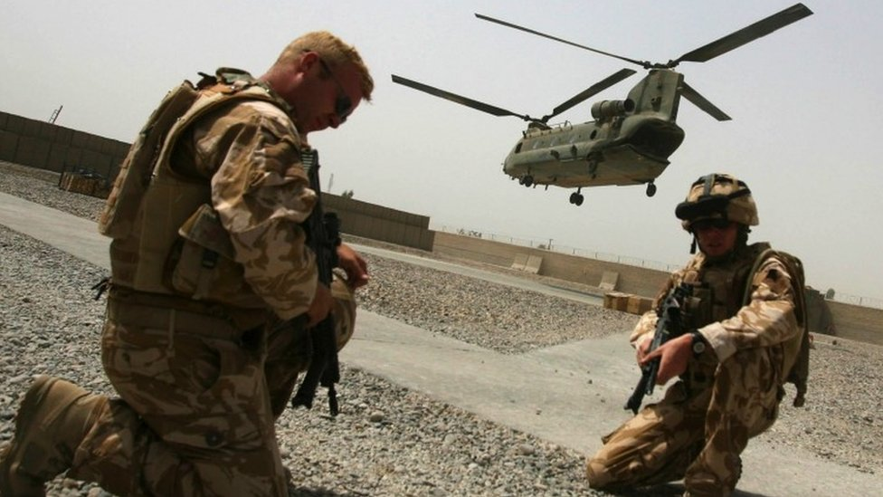 A Chinook helicopter can be seen taking off in the background with troops in the foreground