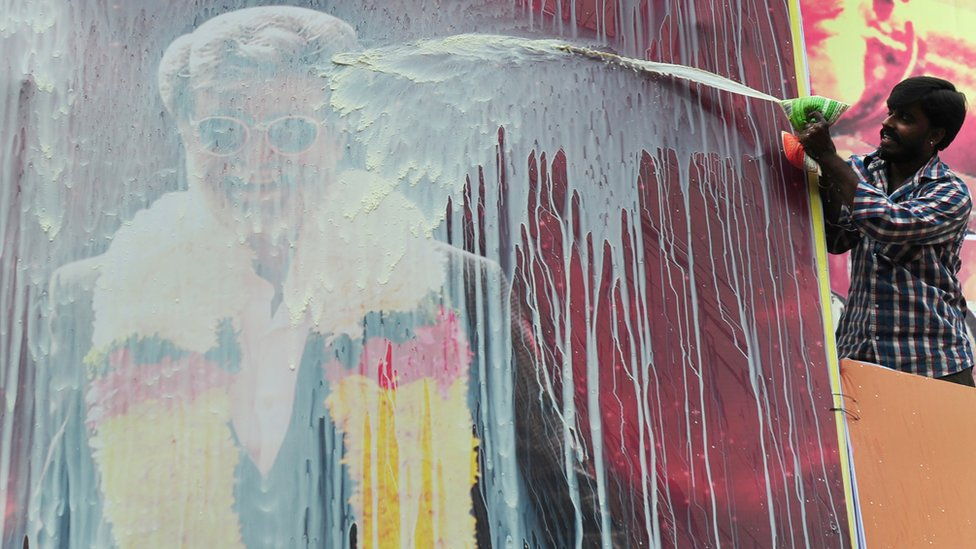 An Indian fan pours milk on a hoarding of Indian movie star, Rajinikanth erected in front of a movie theatre, ahead of the release of his Tamil movie 'Kabali', in Chennai on July 21, 2016