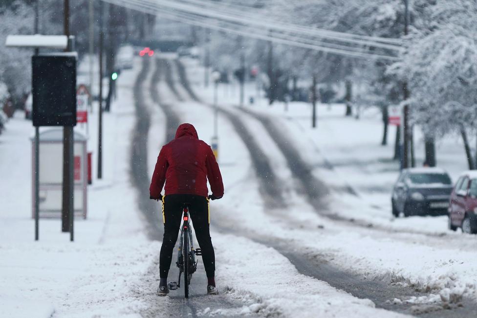 راكب دراجة يسير على طريق مغطى بالثلوج في ستوربريدج ، بعد تساقط الثلوج بغزارة في ويست ميدلاندز