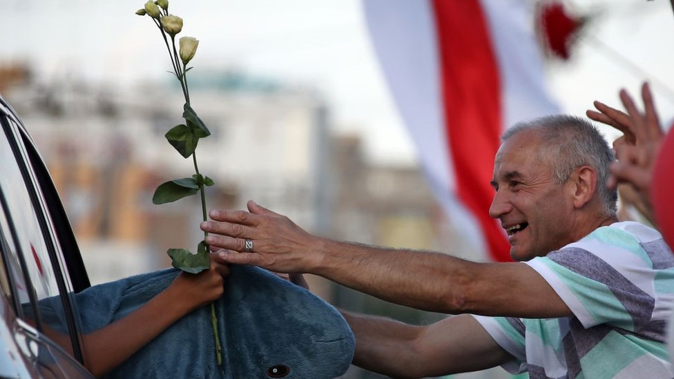 A man presents flowers to passing cars' passengers during an opposition event