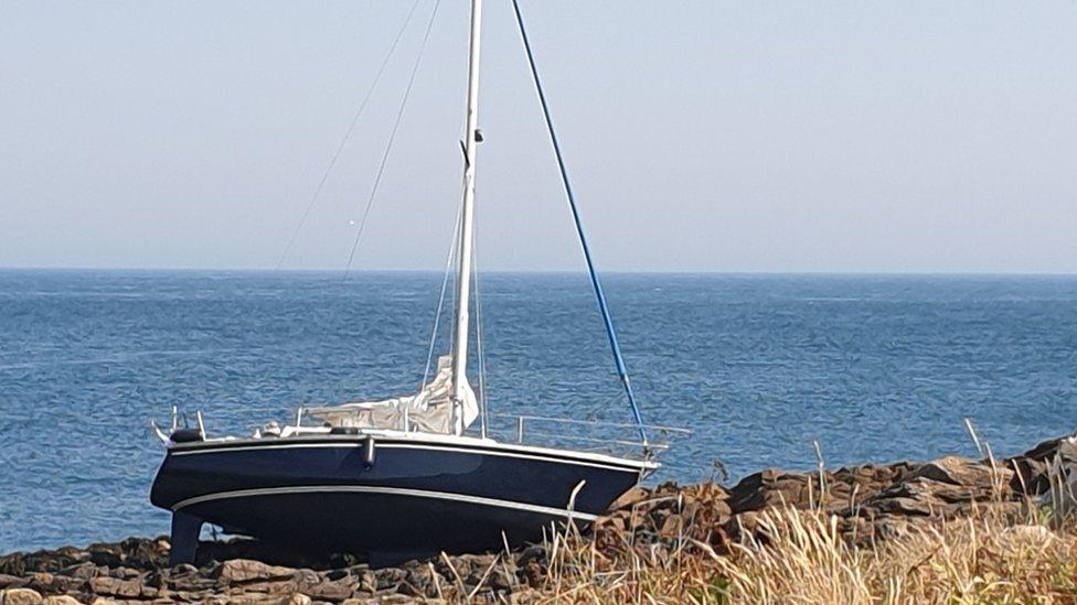 Yacht on a rocky gully off Raz at Longis Bay, Alderney