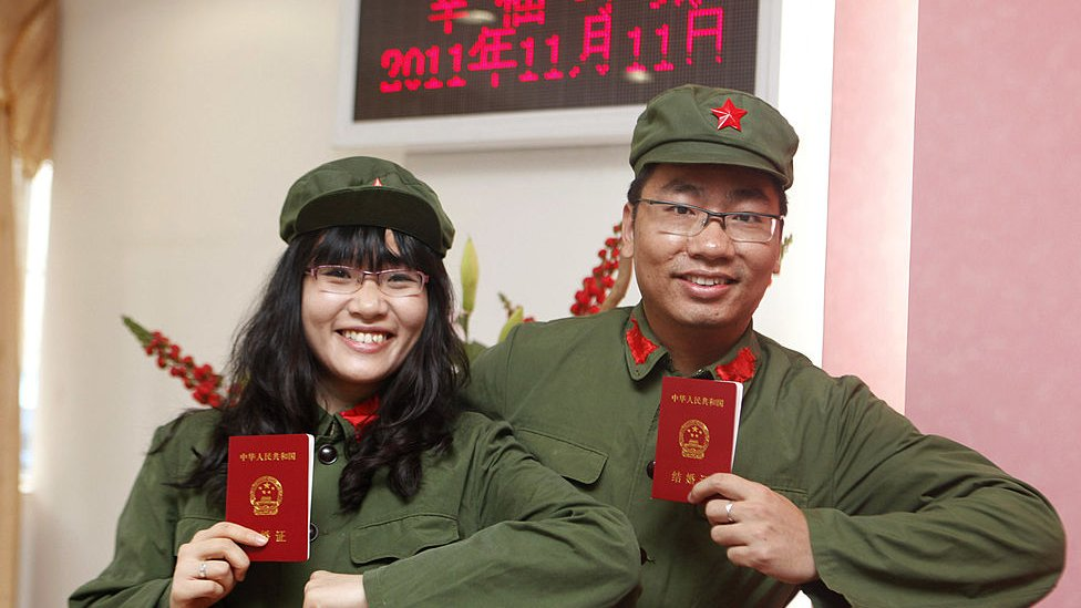 Couple in fancy dress shows their marriage certificates