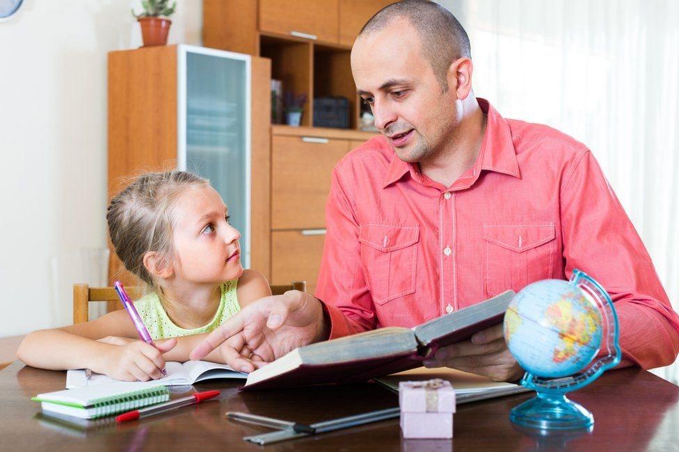 Adulto dándole clases a una niña.