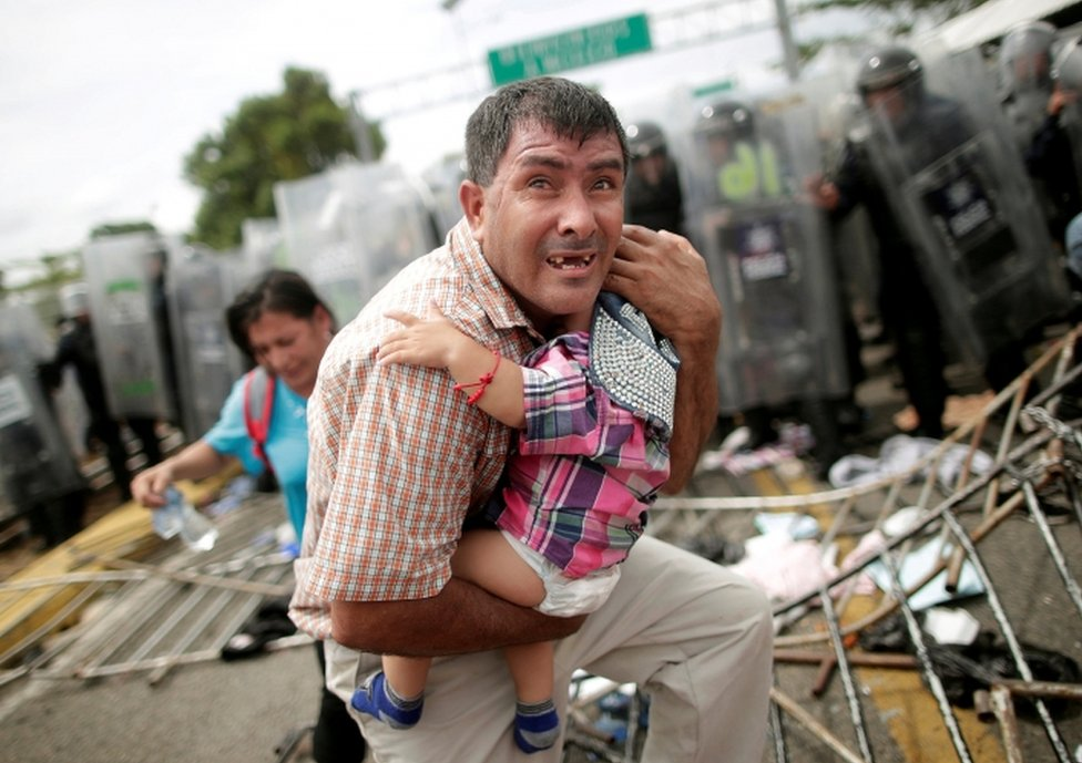 A Honduran man protects his baby amid clashes between migrants and Mexican Police