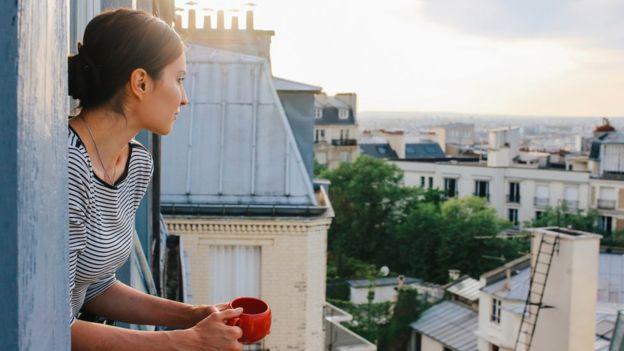Devojka pije kafu na prororu u rano jutro