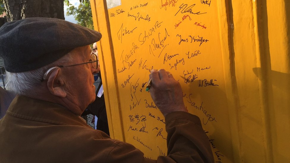 Local resident signing name on phone box