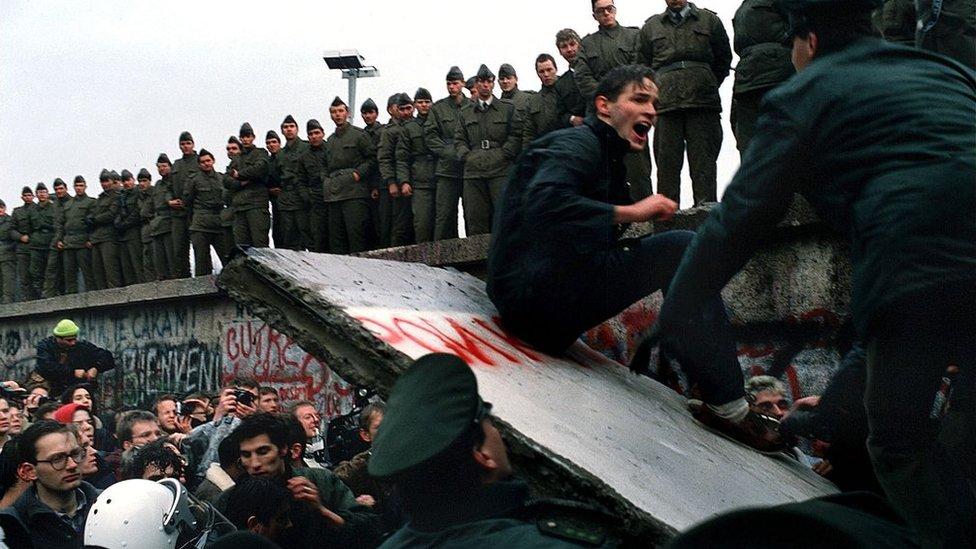 رجل يجلس على جزء متهدم من سور برلين