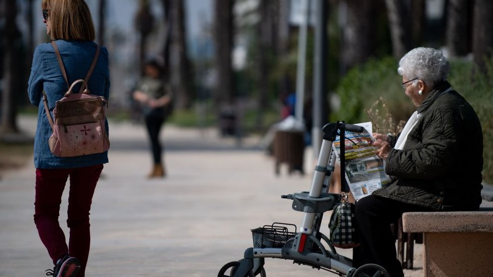 Una mujer de la tercera edad leyendo el periódico en un parque.