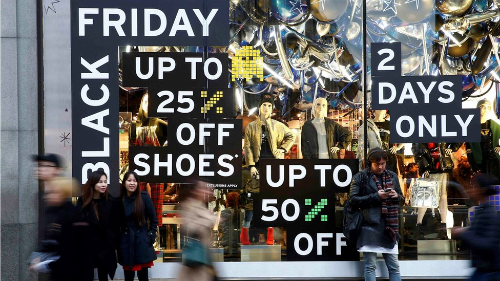 "Shoppers walk past a store promoting ""Black Friday"" in London"