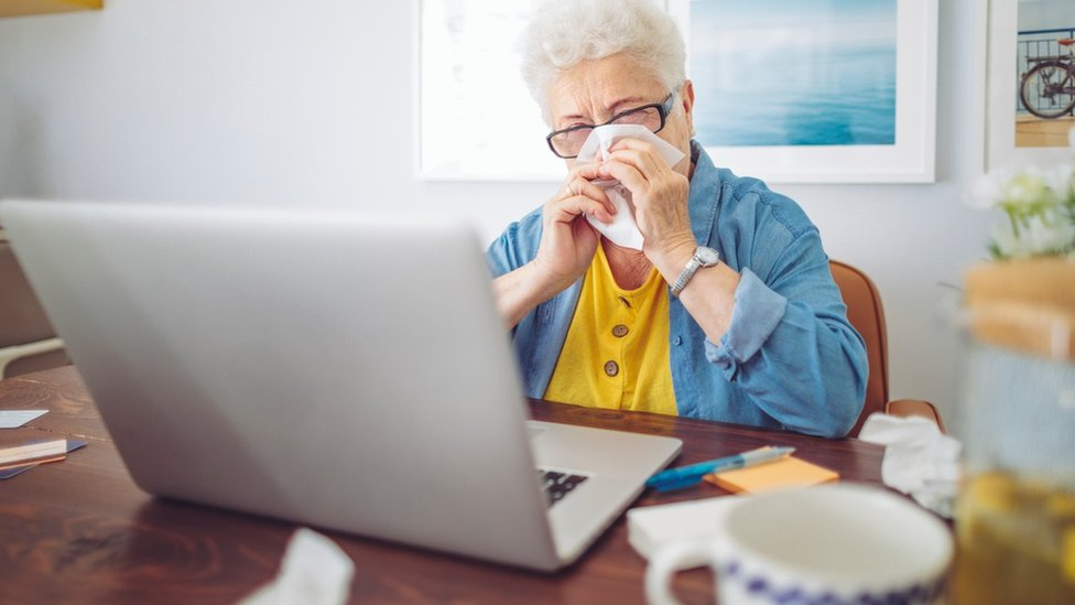Older woman sitting next to laptop