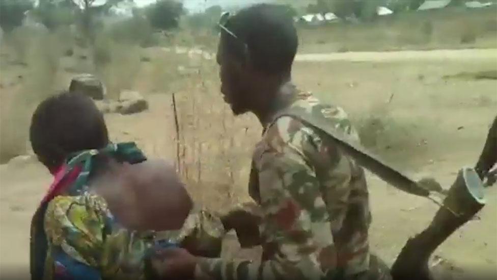 Un soldado empuja a una mujer