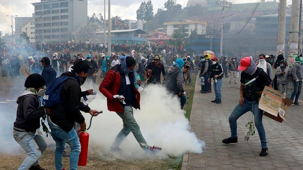 A demonstrator kicks a tear gas canister during a protest against Ecuador's President Lenin Moreno's austerity measures in Quito, Ecuador October 12, 2019