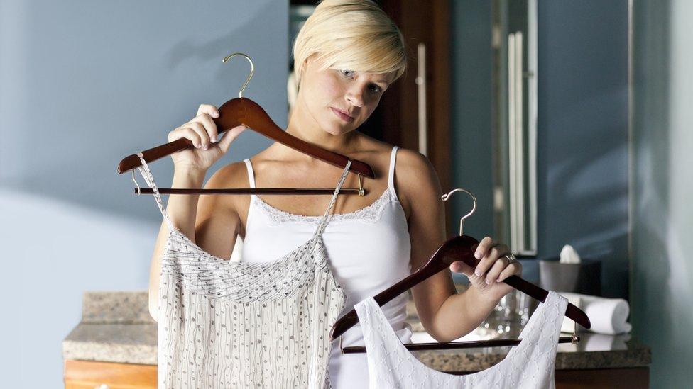 Mujer eligiendo entre dos vestidos