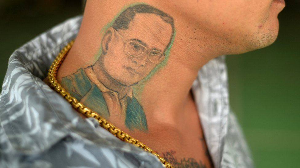 A man poses for a photograph to show his tattoo of Thailand's King Bhumibol Adulyadej in Phuket, Thailand, June 7, 2016.