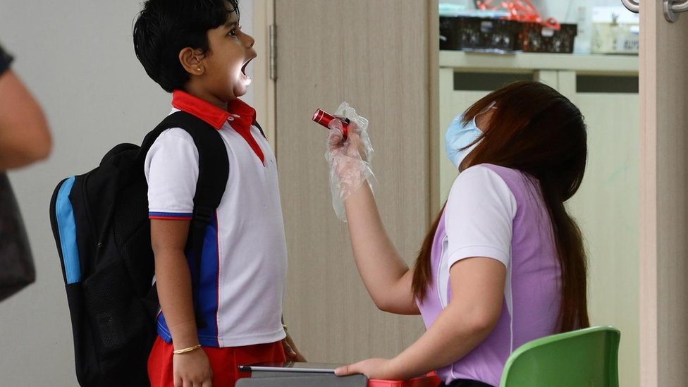 Criança é examinada por mulher com máscara cirúrgica, que aponta lanterna para a sua boca