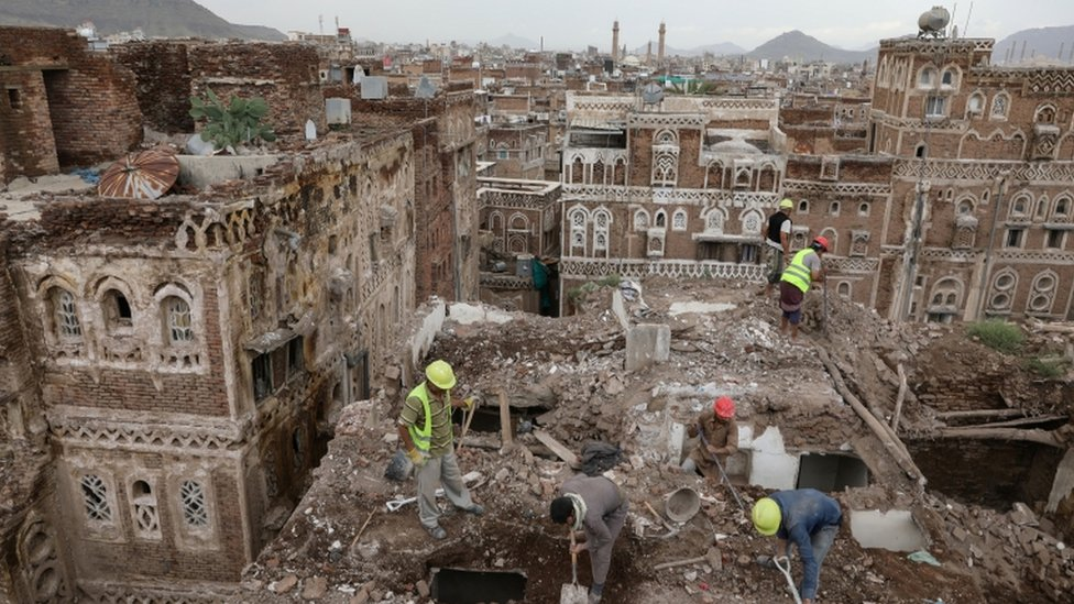 Worker on a roof of a damaged building in the Yemeni capital Sanaa