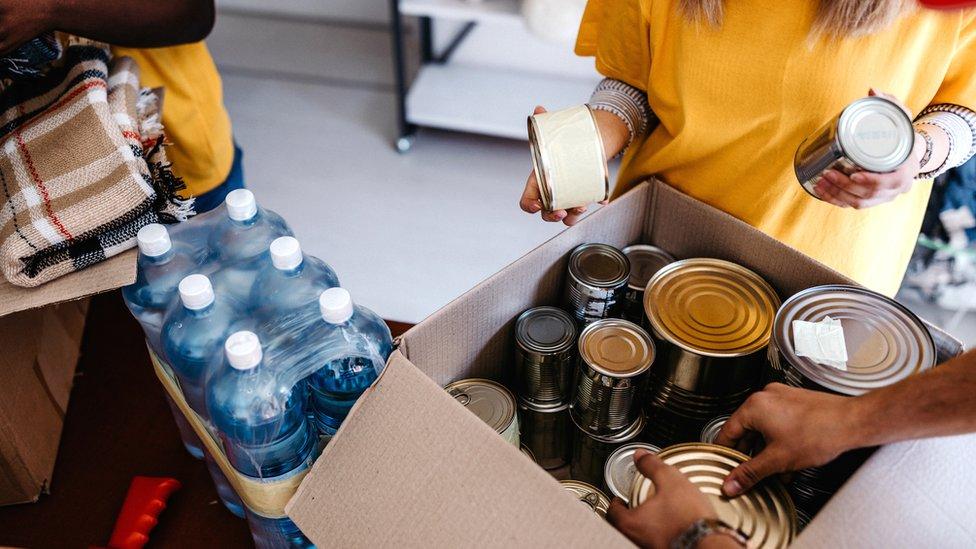 Latas de comida y otros productos en cajas de cartón