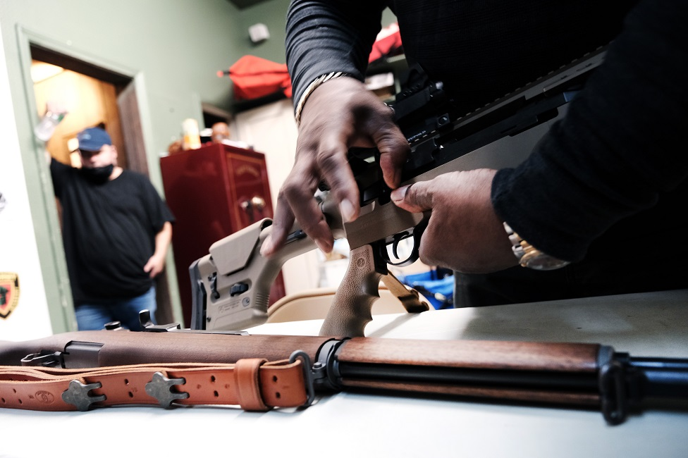 Lateif Dickerson handles some of his rifles at his gun instruction headquarters in New Jersey