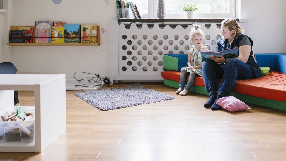 A nursery worker reading with a child